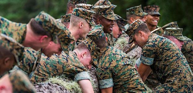 military members holding log